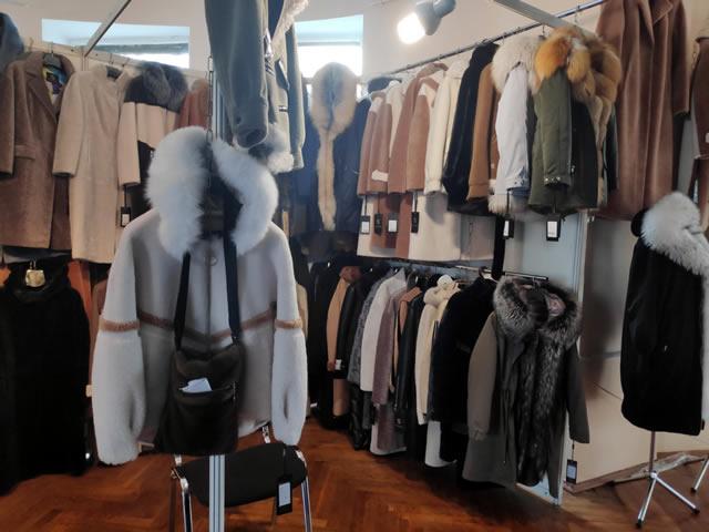 Стенд с пальто, шубами, дубленками и парками с мехом на ярмарке